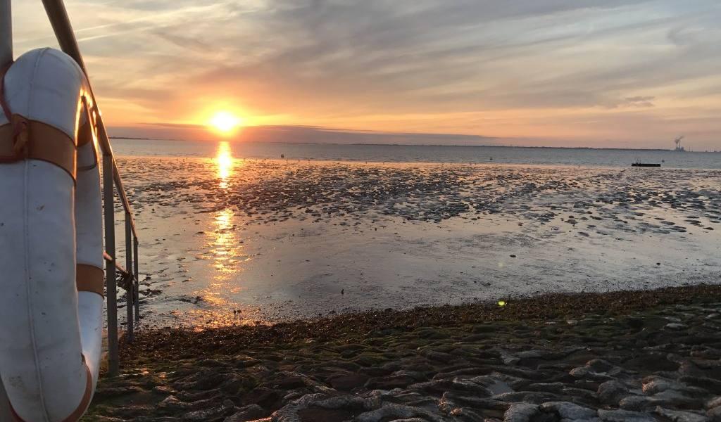 """Die Nordsee-Urlauberin Nina Wacht teilt auf der Online-Plattform """"Entdecke die Nordsee"""" diesen Ausblick auf den Sonnenuntergang in Wremen., © Die Nordsee GmbH"""